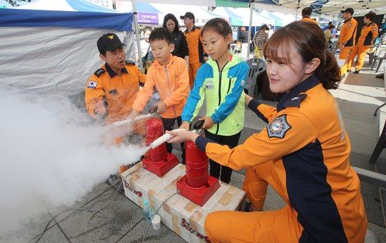2019 위아자 나눔장터 부산행사에 부산소방본부가 마련한 소방활동 체험 부스에서 어린이들이 소화기를 발사하는 체험을 하고 있다. 송봉근 기자