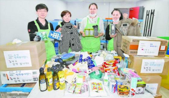 박은진 아름다운가게 부산본부장(오른쪽 둘째)과 직원들이 13일 연제구 아름다운가게 부산본부에서 기증품을 정리하고 있다. 송봉근 기자